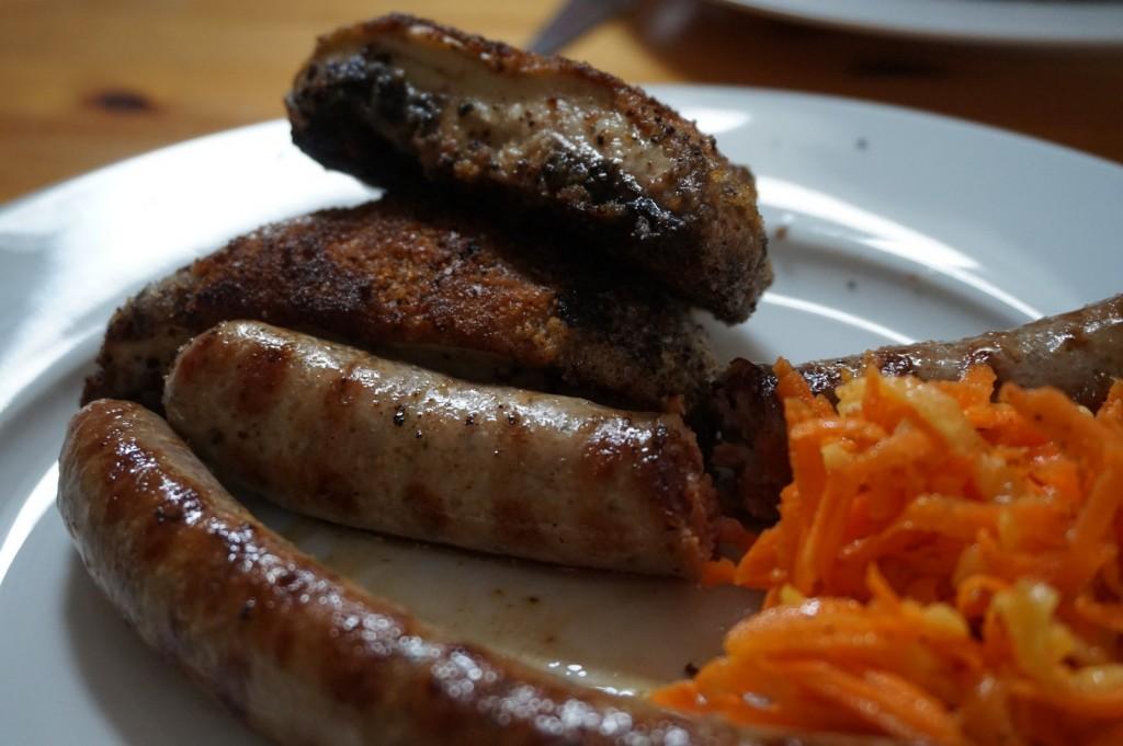 Panierte Rosellas mit Bratwurst und Gelbe-Rüben-Salat.