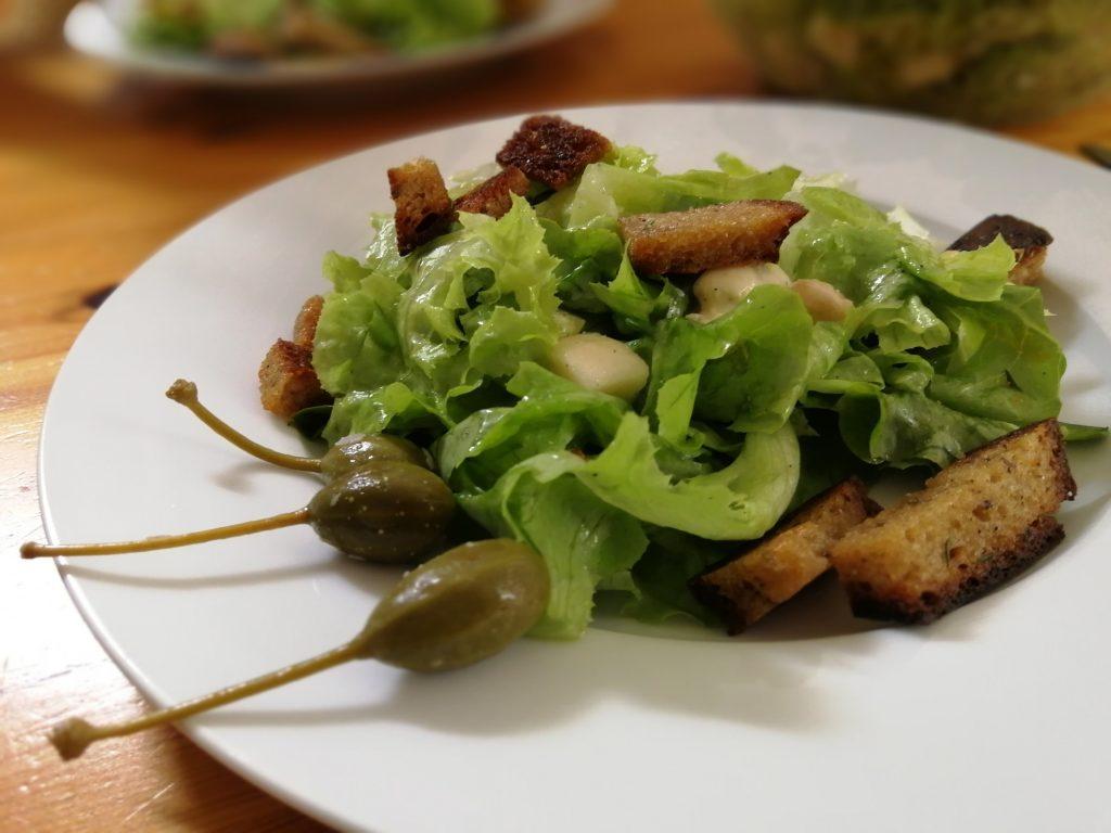 Salat mit warmen Croutons, Gorgonzolawürfeln und Kapernäpfeln.